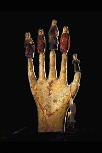 An image of a sculpted hand, with carved figures who stand at the top of each fingertip.