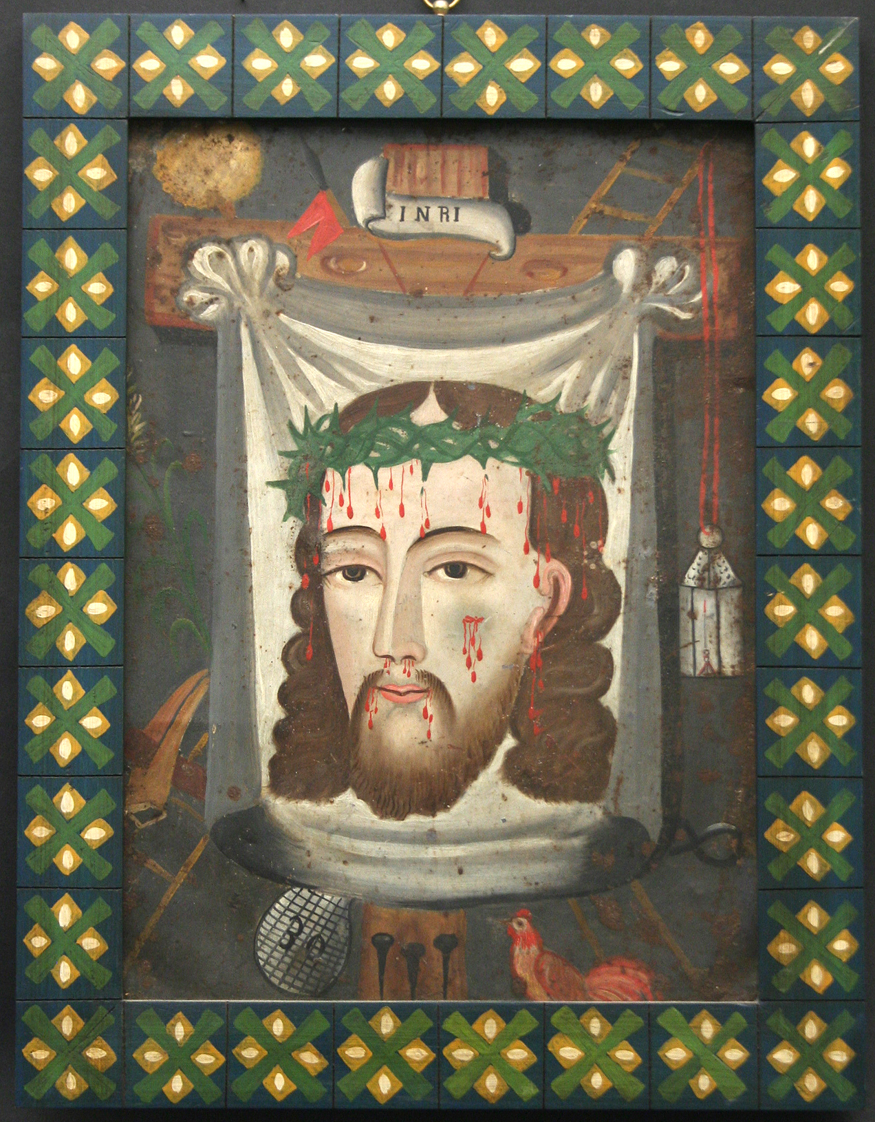 Man's face with long brown hair and beard. Wears a crown of thorns and has blood dripping from his forehead, cheek, nose, and mouth. The face is on a sheet and the sheet is hanging on a wooden cross. The cross is surrounded by holy objects related to the Crucifixion of Jesus Christ.
