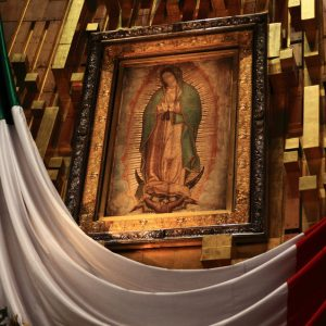 Image depicts a painting of La Virgen de Guadalupe exhibited behind a Mexican flag.